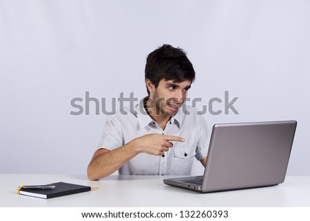 Young modern businessman pointing to his laptop - stock photo
