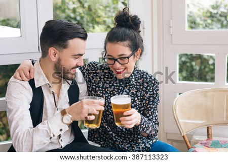 Young modern couple toasting with beer - stock photo