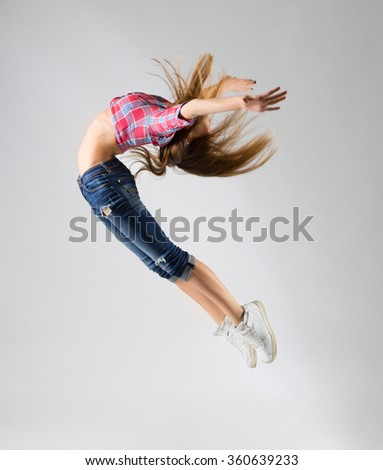 Young modern dancing girl in jeans on grey - stock photo