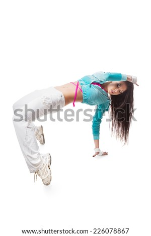 Young modern flexible hip-hop dance girl bends backwards bridge pose with hanging hair. Female in white sweatpants and a turquoise hoodie and sneakers standing on isolated white background. - stock photo