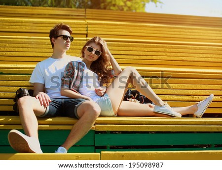 Young modern stylish hipsters couple rest on the bench in city park, sunny portrait couple teenagers in summer day - stock photo