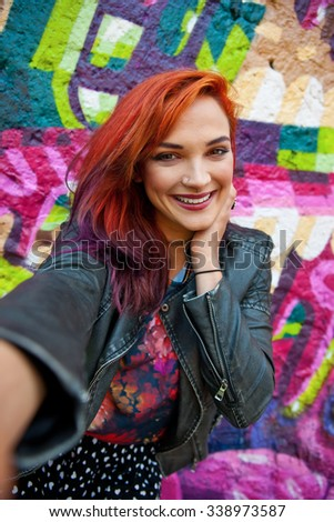 young modern urban girl with red hair in front of graffiti wall making selfie with her phone - stock photo