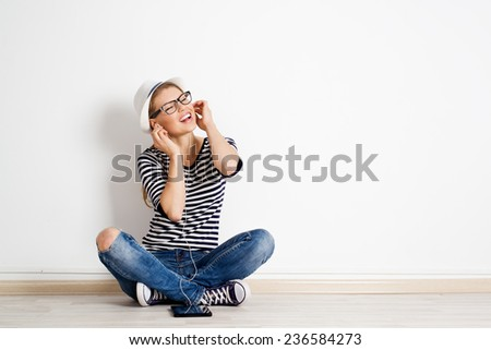 Young modern woman sitting on empty floor with ipad and singing songs. Portrait of funny girl with tablet pc and headset. Teenage lifestyle concept.  - stock photo
