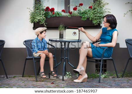 Young mom and her son in street cafe - stock photo