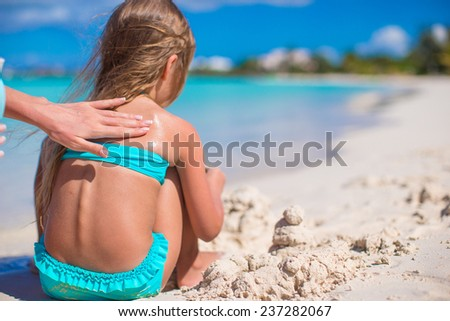 Young mom applying sunblock cream on little daughter's shoulders - stock photo