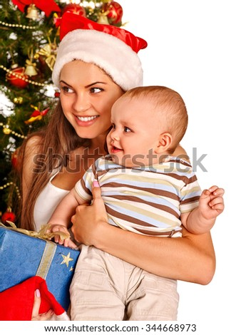 Young mom wearing Santa hat holding  baby boy son with gift box  under Christmas tree on isolated. - stock photo