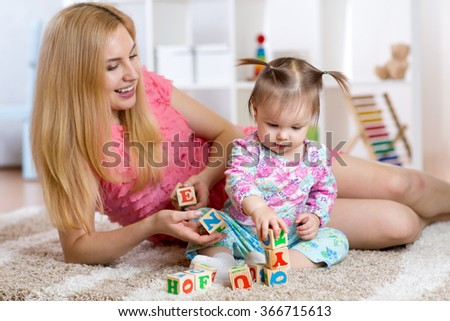 Young mom with her child play together - stock photo