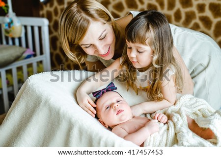 Young mom with her 5 years old daughter and 2 months old baby  and playing in the bed at the weekend together - stock photo