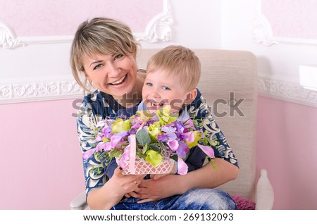 Young mommy and little son with basket of flowers indoors - stock photo