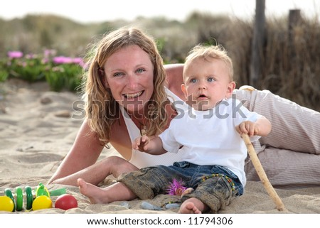 young mommy playing with her son on the beach - stock photo