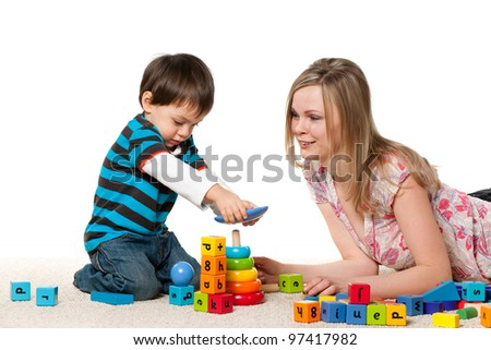 Young mother and a little son are playing on the carpet with blocks - stock photo