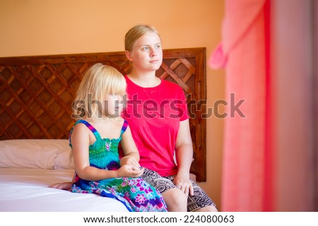 young mother and adorable daughter sit on bed in tropical beach resort room, look at window - stock photo