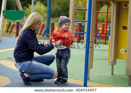 Young mother and baby boy playing on the playground in the autumn park - stock photo