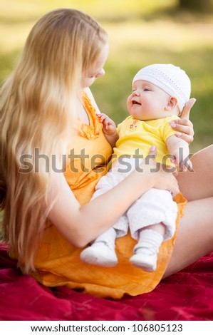 young mother and baby outdoor on a warm summer day (focus on the child) - stock photo