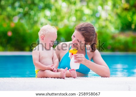 Young mother and cute baby boy enjoying summer vacation in a tropical resort at a swimming pool, parent applying sun screen using lotion spray for safe tan and skin care - stock photo