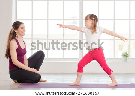Young mother and daughter doing yoga exercise in fitness studio with big windows on background. Happy mother watching the daughter, doing gymnastics - stock photo