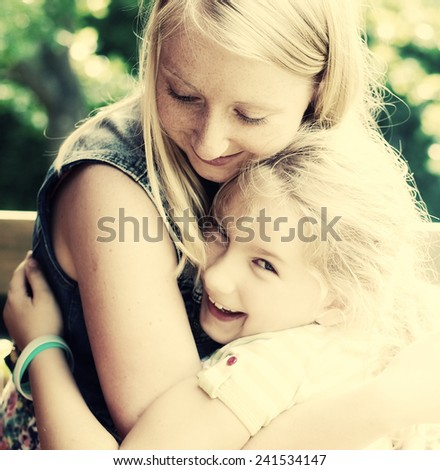 Young mother and daughter. Happy family in garden. - stock photo