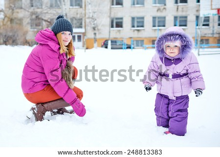 Young mother and daughter laughing for a walk in winter park - stock photo