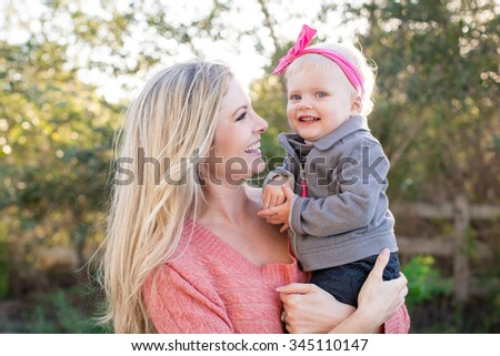 Young mother and daughter outside together - stock photo