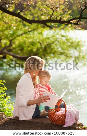 Young mother and daughter reading book and relaxing near the lake - stock photo