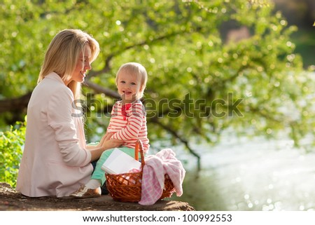 Young mother and daughter reading  relaxing near the lake - stock photo