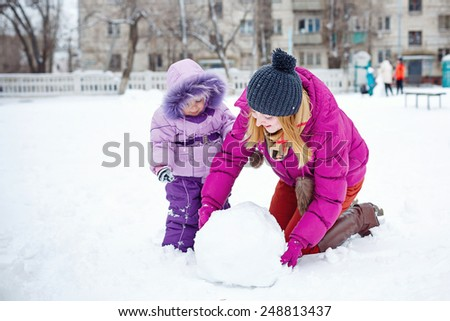 Young mother and daughter sculpt snow snowman in winter park on a sunny day. - stock photo