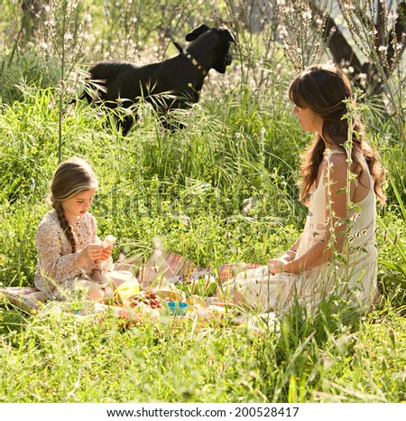 Young mother and daughter sitting and relaxing together in a sunny field of long grass and flowers having a picnic and enjoying a summer holiday with their pet dog. Eating family activities lifestyle. - stock photo