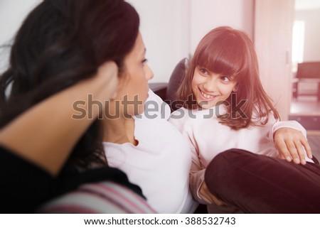 Young mother and daughter sitting on the sofa at home in white lit room against the window. Smooth morning light, casual style - concept of happy family living and lifestyle - stock photo