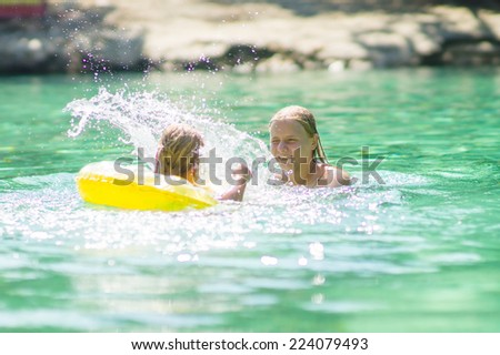 Young mother and daughter swimming with inflatable ring in crystal clear laguna on tropical island - stock photo