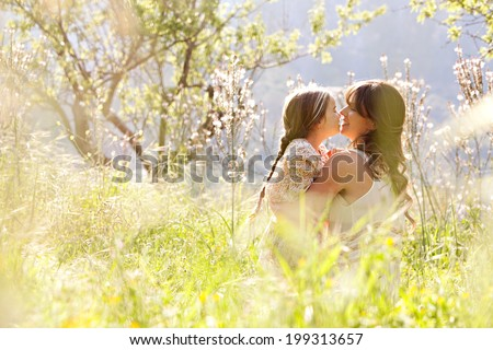 Young mother and daughter together, hugging and kissing while sitting and relaxing in a golden field of sunshine and spring flowers while on a summer holiday. Family activities and outdoors lifestyle. - stock photo