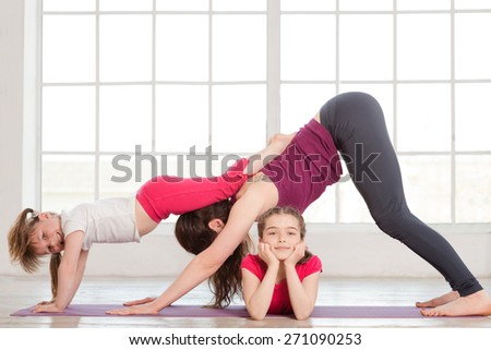 Young mother and daughters doing yoga exercise in home with big windows on background - stock photo
