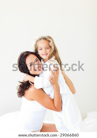 Young Mother and daugther embracing on bed - stock photo