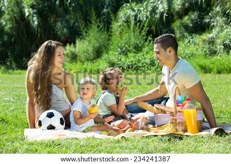 Young mother and father with little daughters having holiday with picnic - stock photo