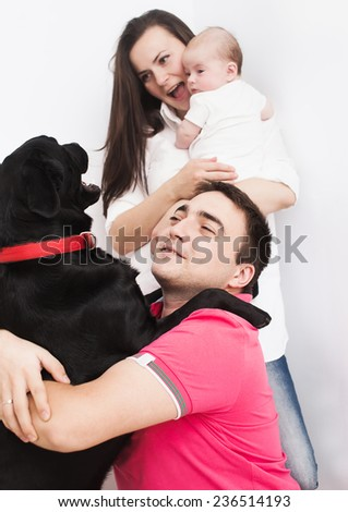Young mother and father with newborn baby playing with dog - stock photo