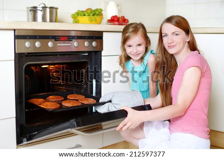 Young mother and her adorable little daughter baking cookies at home in a kitchen - stock photo
