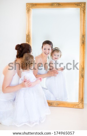Young mother and her adorable toddler daughter in a white dress standing in front of a big mirror - stock photo