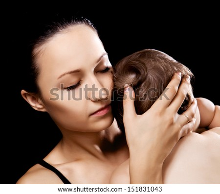 young mother and her baby in the studio, isolated on black background - stock photo
