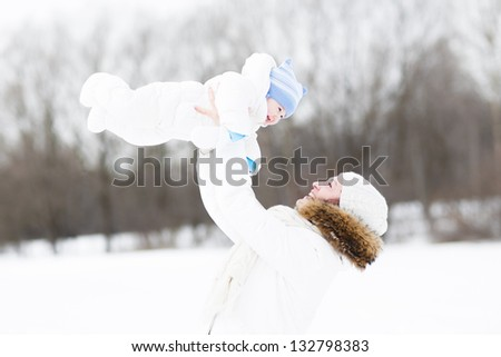 Young mother and her baby playing in the snow - stock photo