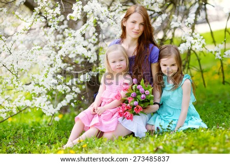 Young mother and her children in blooming cherry garden on beautiful spring day - stock photo