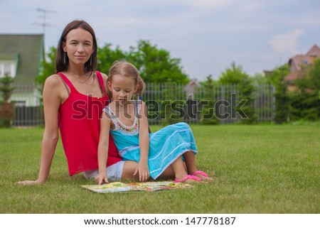 young mother and her cute daughter reading a book and enjoying the holiday - stock photo
