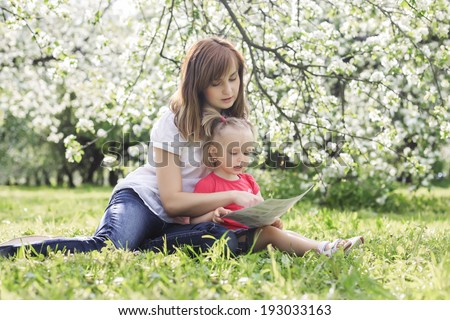 young mother and her cute daughter reading book and enjoying holiday - stock photo