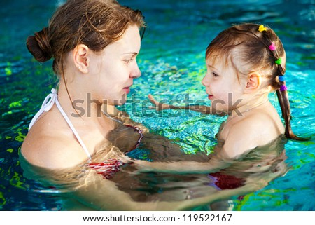 Young mother and her cute little daughter swimming in the pool - stock photo