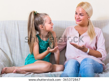 Young mother and her cute little daughter talking and laughing at home - stock photo