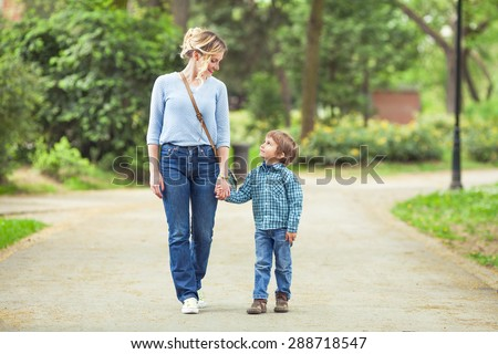 Young mother and her cute little son walking in a park - stock photo