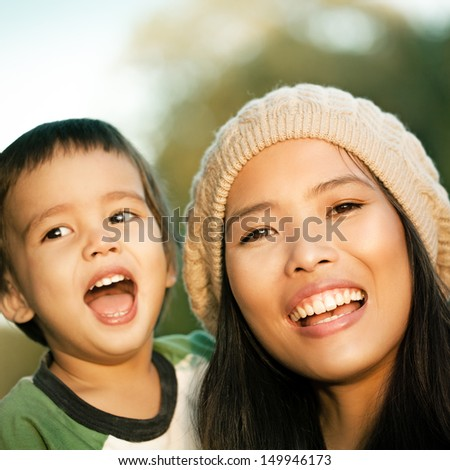 Young mother and her cute son smiling together on an autumn day. - stock photo