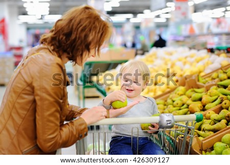 Young mother and her cute toddler boy in a food store or a supermarket  - stock photo