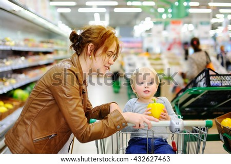 Young mother and her cute toddler son in a food store or a supermarket  - stock photo