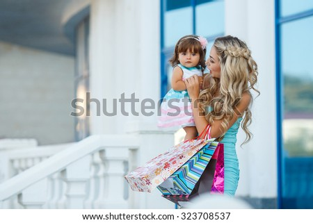 Young mother and her daughter doing shopping together. Woman with child on shopping in shopping mall with bags. Mother with baby girl with shopping bags with mall on background. Fashion and beauty.  - stock photo