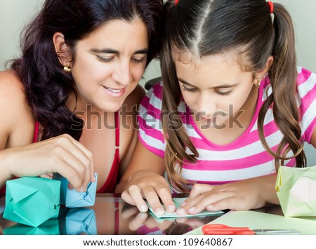 Young mother and her daughter making paper models or origami - stock photo
