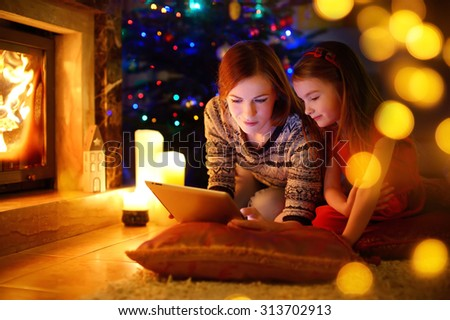 Young mother and her daughter using a tablet pc by a fireplace on warm Christmas evening - stock photo